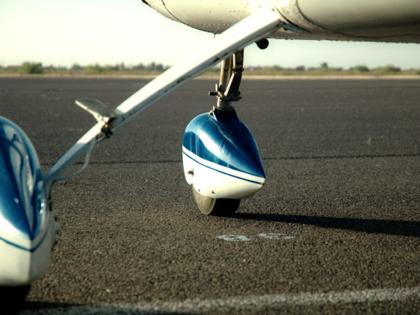A small single engine cessna parked on the ramp.