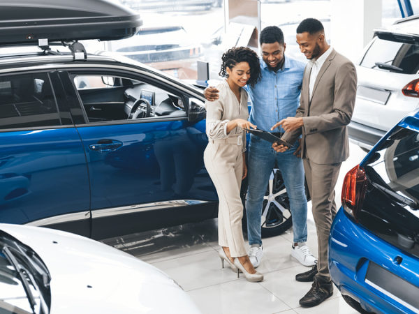 Black Couple Visiting Car Dealership Buying New Vehicle Talking With Salesman Standing In Auto Showroom. Happy Buyers. Panorama, Free Space
