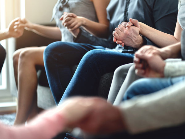 Group therapy, peer support and psychology session. Trust, unity and empathy concept. Empowering community. Hope, help and friendship. Team empowerment. Happy people sitting in circle holding hands.