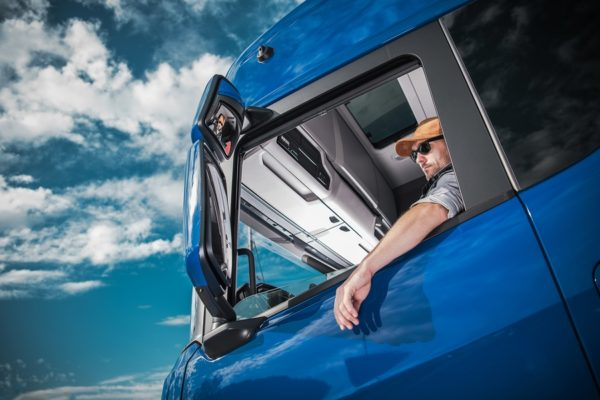 Heavy Load Cargo Delivery. Caucasian Truck Driver Inside Semi Tractor Cabin and the Blue Sky. Transportation Industry.