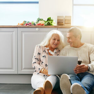 Older couple sitting on floor looking at computer_edited