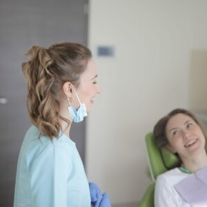 dentist and client in office for routine oral health exam