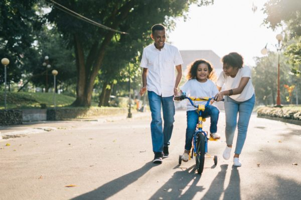 family parents and child riding bike