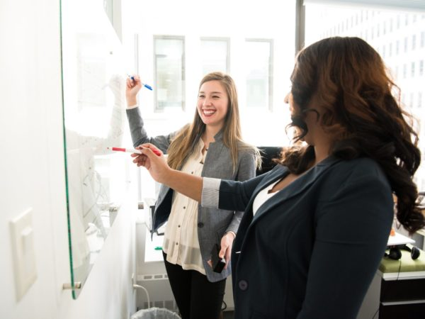 two women coworkers smiling using whiteboard