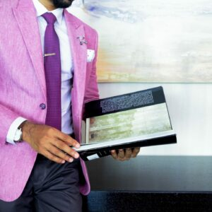 young professional in bright pink suit reading book