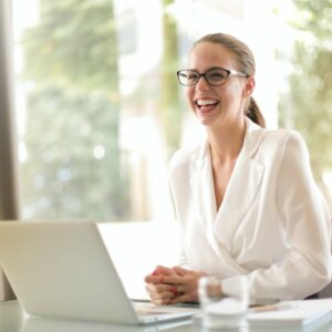 young professional woman smiling in front of laptop