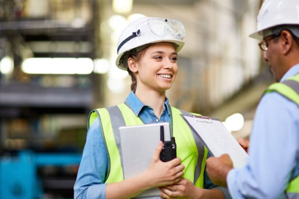 factory employee holding clipboard and walkee talkie with hard hat and safety vest
