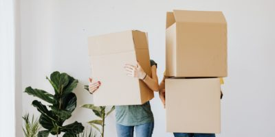 young couple holding boxes moving in