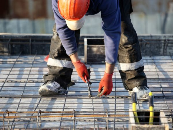 construction worker bending down for wire
